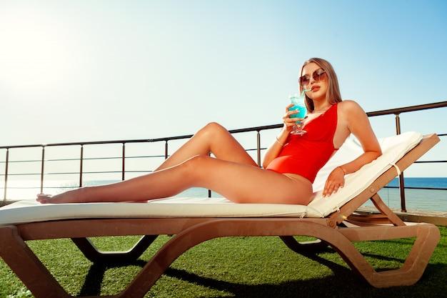 Bella donna con un corpo perfetto, prendere il sole sul lettino