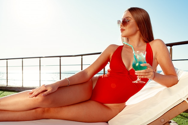 Bella donna con un corpo perfetto, prendere il sole sull'amaca