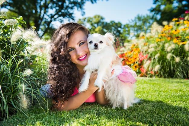 Bella donna con un piccolo cane chihuahua nel parco