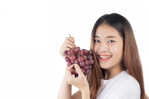 Bella donna con un sorriso felice che tiene un'uva della mano, isolata su fondo bianco.