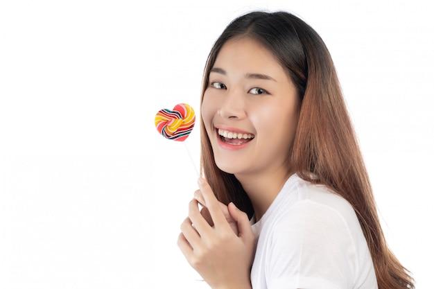 Bella donna con un sorriso felice che tiene una caramella della mano, isolata su priorità bassa bianca.