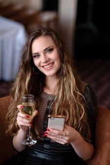 Bella donna con un telefono e un bicchiere di champagne