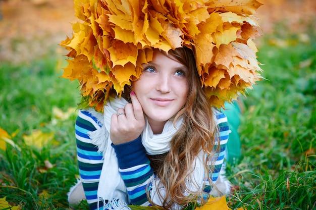 Bella donna con una corona di foglie gialle sdraiato sull'erba