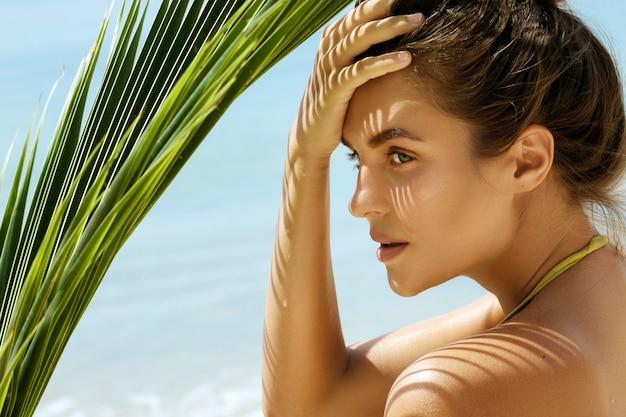 Bella donna con una foglia di palma sulla spiaggia