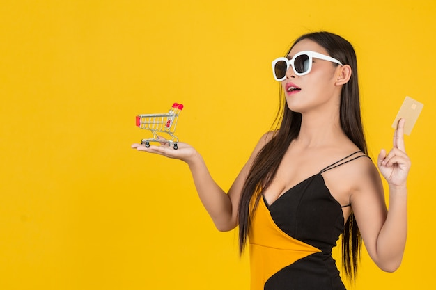 Bella donna d'acquisto che tiene un carrello in sua mano su un giallo.