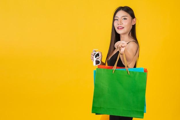 Bella donna d'acquisto che tiene un sacco di carta variopinto su un giallo.