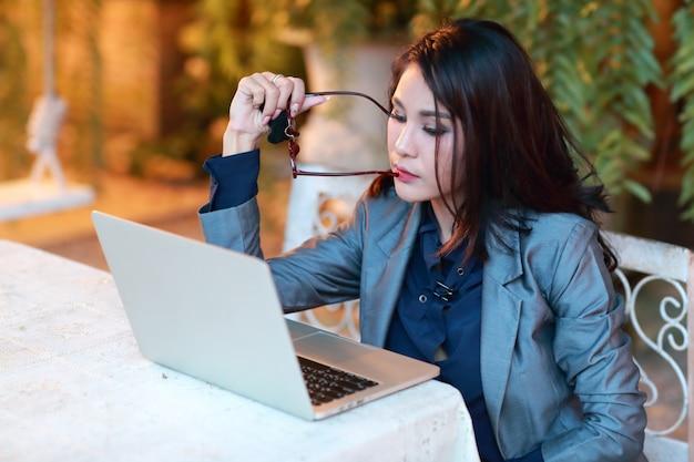 Bella donna d'affari asiatiche con gli occhiali lavorando e pensando sul computer portatile