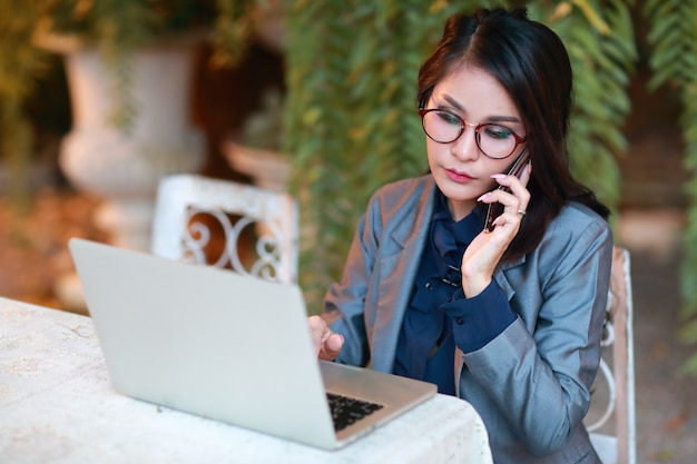 Bella donna d'affari asiatiche con gli occhiali lavorando su computer portatile e telefono cellulare