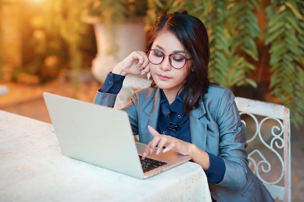 Bella donna d'affari asiatiche con gli occhiali lavorando sul computer portatile
