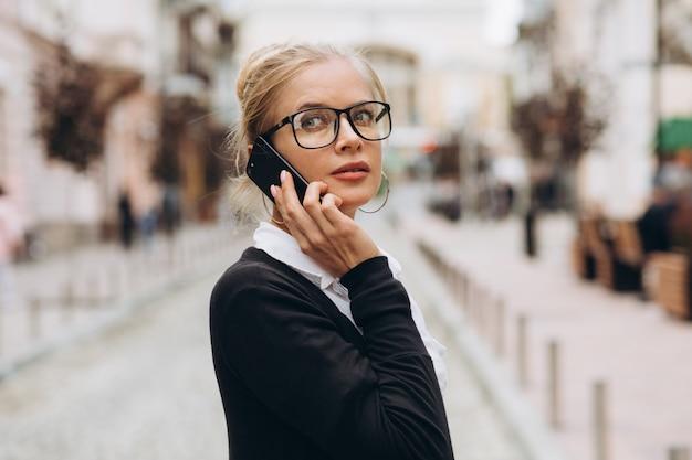 Bella donna d'affari bionda alla moda in bicchieri con smartphone e borsetta di documenti nelle sue mani all'aperto.