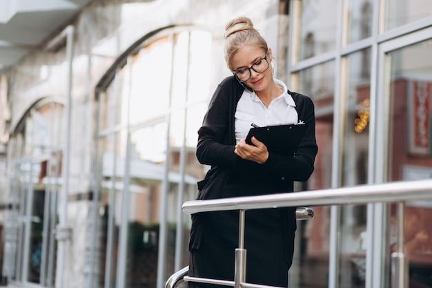Bella donna d'affari bionda alla moda in occhiali parlando dal telefono cellulare e in piedi al di fuori di un edificio per uffici.