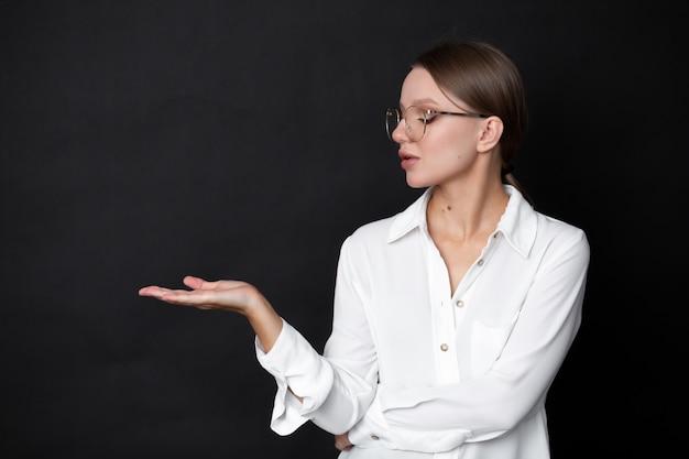 Bella donna d'affari in bicchieri su un muro nero tese la mano su cui è possibile disegnare grafica