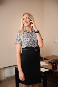 Bella donna d'affari parlando sul cellulare. giovane lavoro di modello femminile con le vendite in ufficio luminoso.