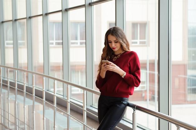 Bella donna d'affari scrivere sms su un telefono cellulare.