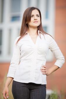 Bella donna d'affari sulla parete dell'ufficio moderno