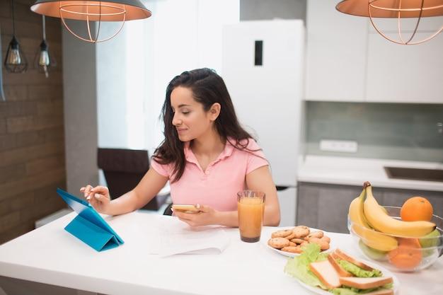 Bella donna dai capelli neri lavora da casa. un dipendente si siede in cucina e ha molto lavoro su un laptop e tablet e ha videoconferenze e riunioni