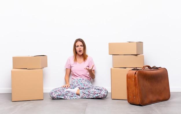 Bella donna dai capelli rossi che sembra arrabbiata, irritata e frustrata, urlando o cosa c'è di sbagliato in te in una nuova casa