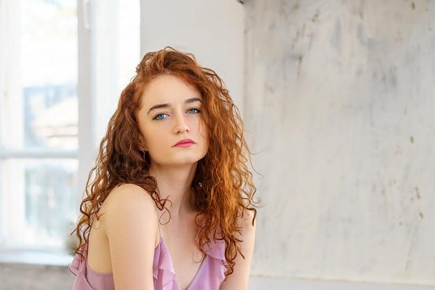 Bella donna dai capelli rossi che si siede in studio in un umore triste.