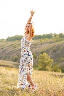 Bella donna dai capelli rossi si diverte e balla in un campo al tramonto