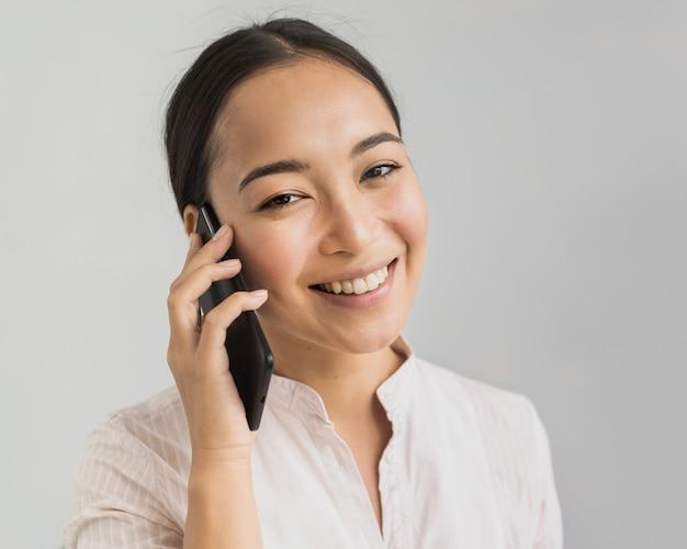 Bella donna del ritratto che parla sopra il telefono