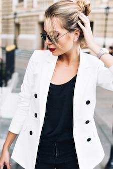 Bella donna del ritratto in occhiali da sole sulla strada. sta toccando i capelli, guardando in basso.