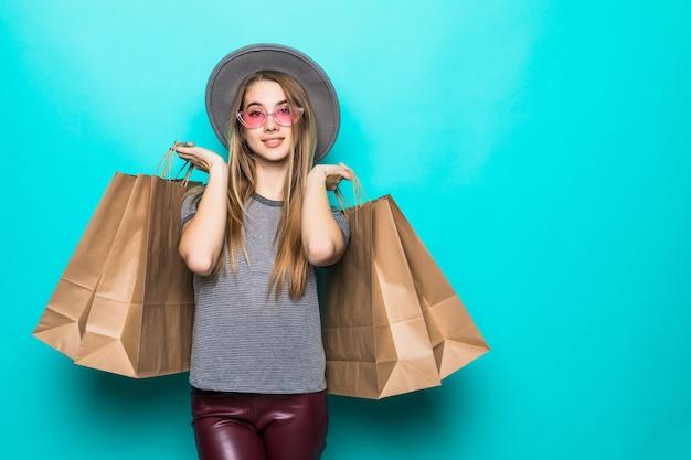 Bella donna dello shopping sorridente e indossa un cappello isolato su sfondo verde