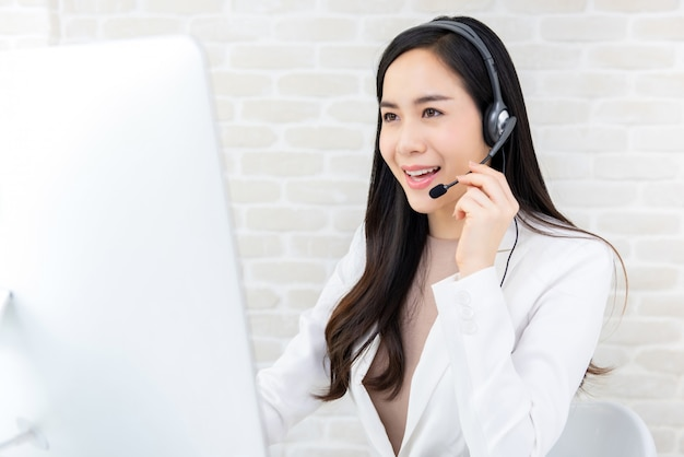 Bella donna di affari asiatica che lavora nella call center come operatore
