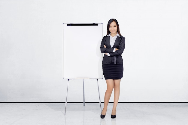 Bella donna di affari asiatica che si leva in piedi con la lavagna