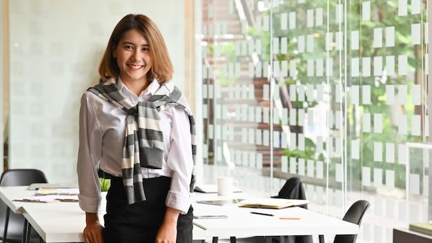 Bella donna di affari asiatica che sorride con confidenza nella sala riunioni.
