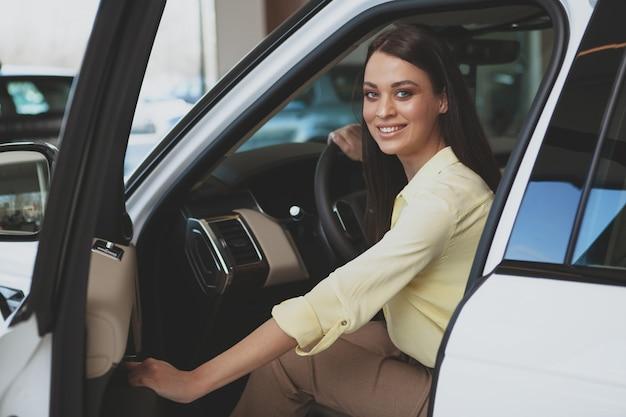 Bella donna di affari che compra nuova automobile