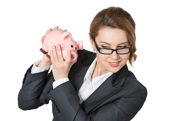 Bella donna di affari sorridente che agita il salvadanaio che controlla la quantità di denaro isolata. concetto di capitale bancario, assicurativo e monetario.