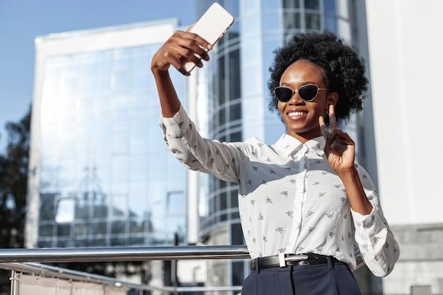 Bella donna di angolo basso che prende i selfie