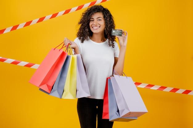 Bella donna di colore africana con i sacchetti della spesa variopinti e carta di credito isolata sopra giallo con nastro adesivo