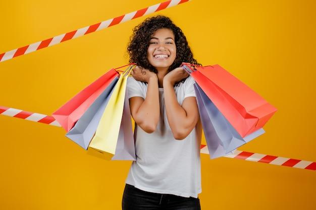 Bella donna di colore africana con i sacchetti della spesa variopinti isolati sopra giallo con nastro adesivo