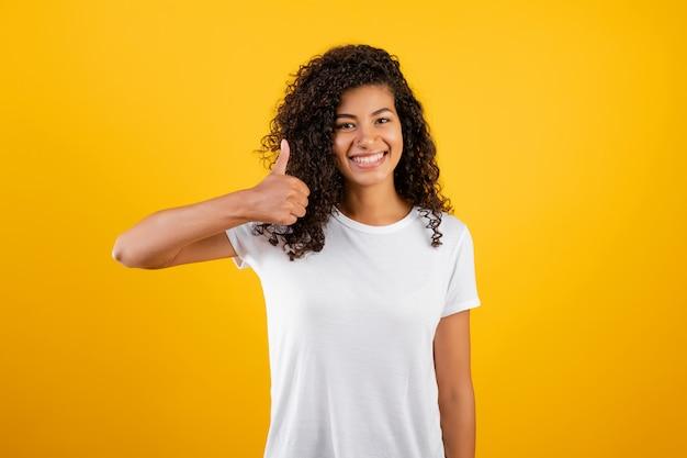 Bella donna di colore che mostra i pollici in su isolati sopra giallo