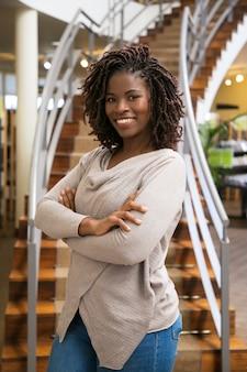 Bella donna di colore che posa alla biblioteca