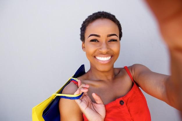 Bella donna di colore che sorride con i sacchetti della spesa che prendono un selfie