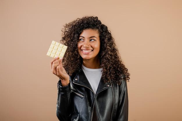 Bella donna di colore con cioccolata bianca isolata sopra marrone