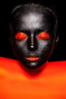 Bella donna di colore in maschera nera con trucco e labbra luminosi arancioni