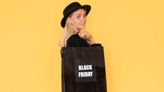 Bella donna di lato che tiene la borsa della spesa venerdì nero