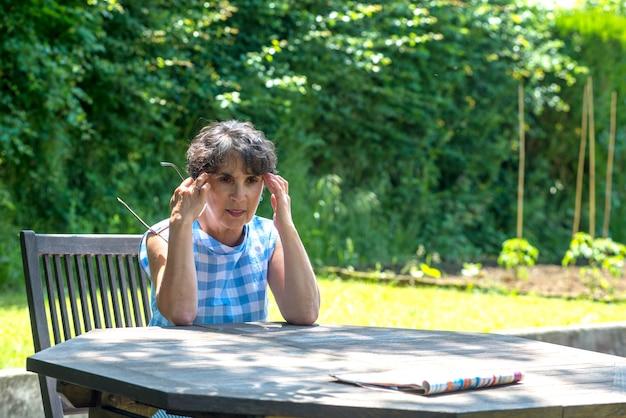 Bella donna di mezza età ha mal di testa in giardino