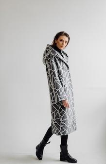Bella donna di modo che posa con il cappotto elegante