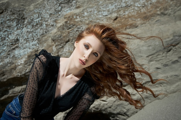 Bella donna di modo che posa vicino alle rocce sabbiose