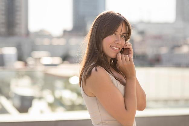 Bella donna di smiley che propone all'aperto
