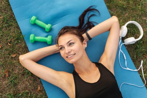 Bella donna di vista superiore che riposa sul tappeto di yoga