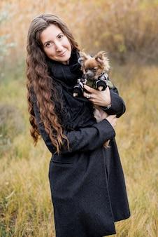 Bella donna e il suo cane nel parco in autunno