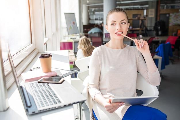 Bella donna è seduta al tavolo vicino alla finestra e mastica una matita. inoltre sta pensando a qualcosa. la ragazza ha un tablet in mano e un computer portatile sul tavolo.