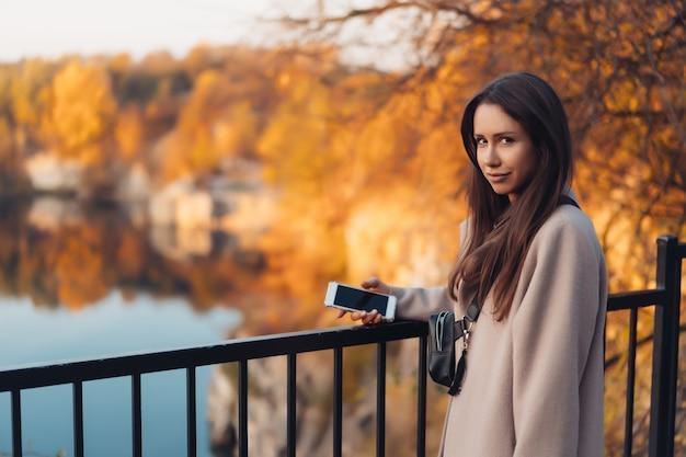 Bella donna elegante che sta in un parco in autunno