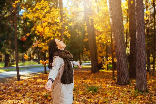 Bella donna elegante nel parco di autunno. foresta gialla d'autunno