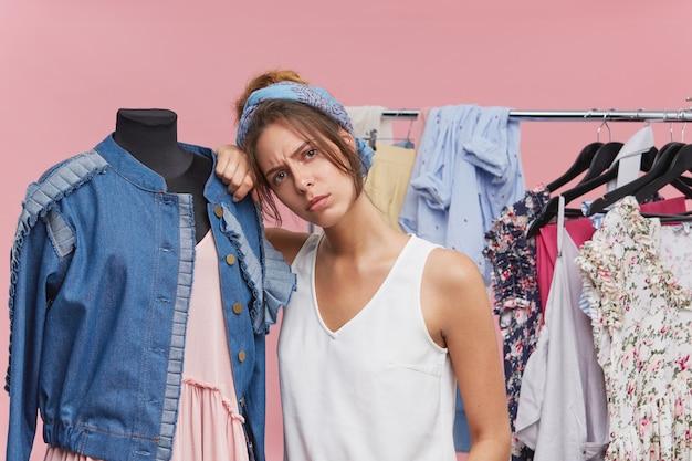 Bella donna esausta in piedi vicino al manichino, avendo un'espressione stanca e triste dopo aver trascorso tutto il giorno nel negozio di abbigliamento, scegliendo un abito adatto a se stessa. venditore annoiato vicino al manichino con i vestiti